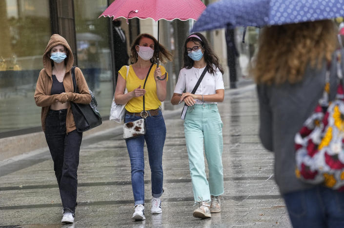 People wearing a face masks to protect against coronavirus walk along the Champs Elysees avenue in Paris, Monday, July 12, 2021. France's President Emmanuel Macron is hosting a top-level virus security meeting Monday morning and then giving a televised speech Monday evening, the kind of solemn speech he's given at each turning point in France's virus epidemic. (AP Photo/Michel Euler)