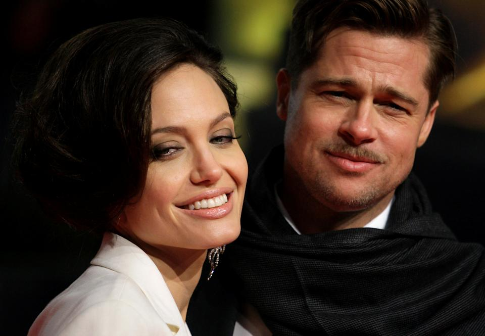 """U.S. actors Brad Pitt and his partner Angelina Jolie pose for photographers on the red carpet at the German premiere of the movie """"The Curious Case of Benjamin Button"""" in Berlin January 19, 2009. (Photo: REUTERS/Hannibal Hanschke)"""