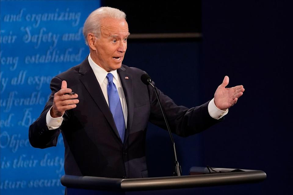 Joe Biden gestures with both hands as he speaks onstage