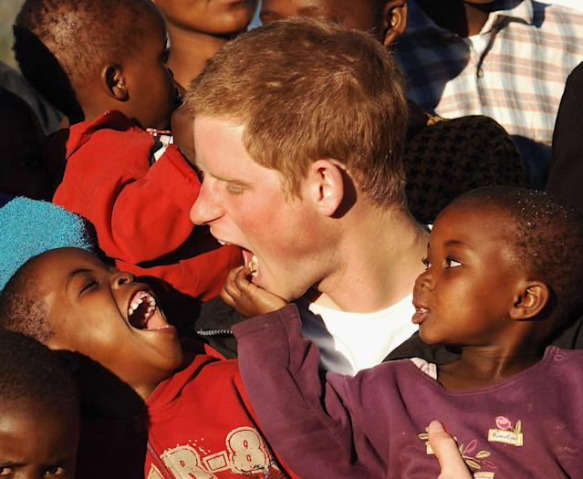 """<p>Prince Harry makes faces at two boys, Mutsu (left) and Lintle (right), in the grounds of the Mants'ase children's home on a return visit to Lesotho on April 24, 2006, in southern Africa. The prince was in the country to launch his new charity, Sentebale, which means """"Forget me not,"""" in memory of his mother, Princess Diana. (Photo by Pool/Anwar Hussein Collection/Getty Images) </p>"""