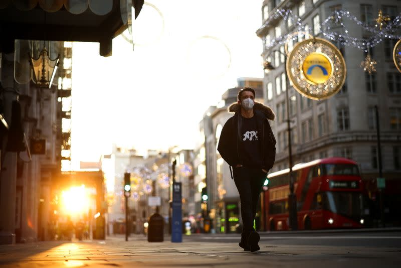 A man wearing a protective face mask walks down Strand during sunset, amid the coronavirus disease (COVID-19) outbreak, in London