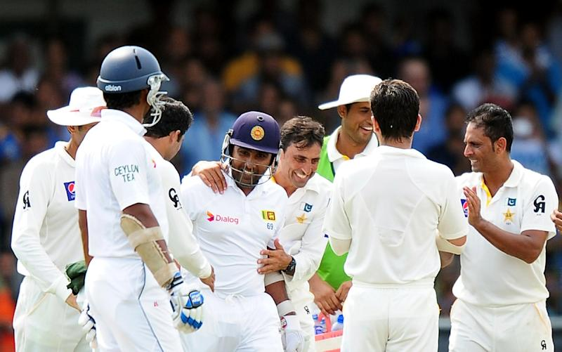 Sri Lanka batsman Mahela Jayawardene (C) is congratulated by Pakistan cricketers as he enters the pitch to bat during the third day of the second Test at The Sinhalese Sports Club (SSC) Ground in Colombo on August 16, 2014 (AFP Photo/Lakruwan Wanniarachchi)