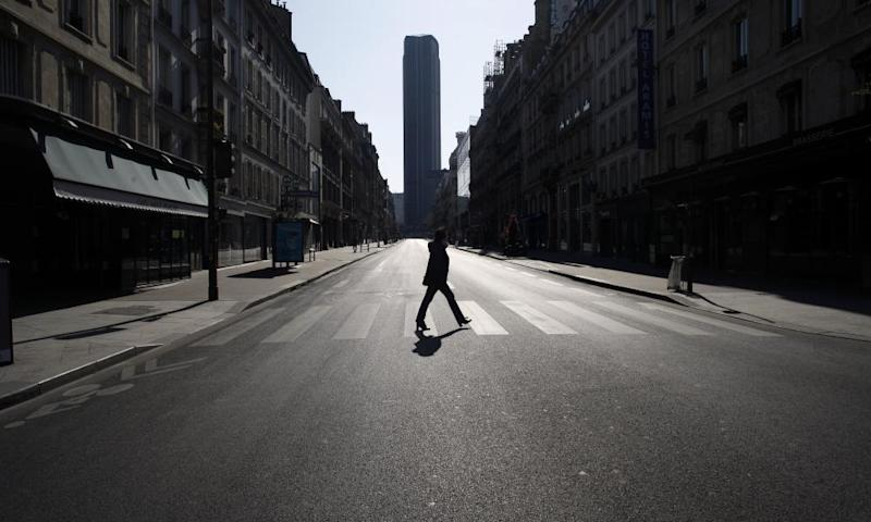 A woman crosses an empty street in Paris during the nationwide confinement.