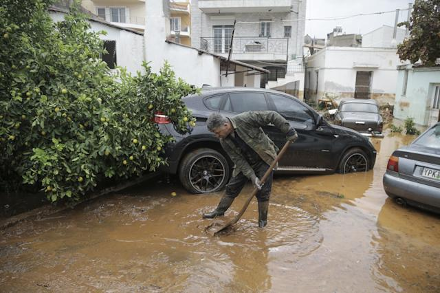 A man tries to remove floodwater from the area after torrential rains.