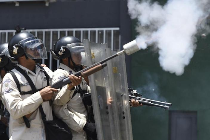 Riot police throw tear gas during clashes with demonstrators against Nicolas Maduro's government in Caracas on April 8, 2017 (AFP Photo/JUAN BARRETO )