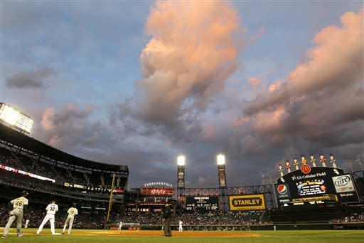 The setting sun illuminates the clouds over U.S. Cellular Field during the third inning of a baseball game between the Chicago White Sox and the Oakland Athletics on Friday, Aug. 10, 2012, in Chicago. (AP Photo/Charles Rex Arbogast)