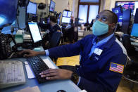 Trader Aaron Ford works on the floor of the New York Stock Exchange, Monday, July 19, 2021. Resurgent pandemic worries knocked stocks lower from Wall Street to Tokyo on Monday, fueled by fears that faster-spreading variants of the virus may upend the economy's strong recovery. (AP Photo/Richard Drew)