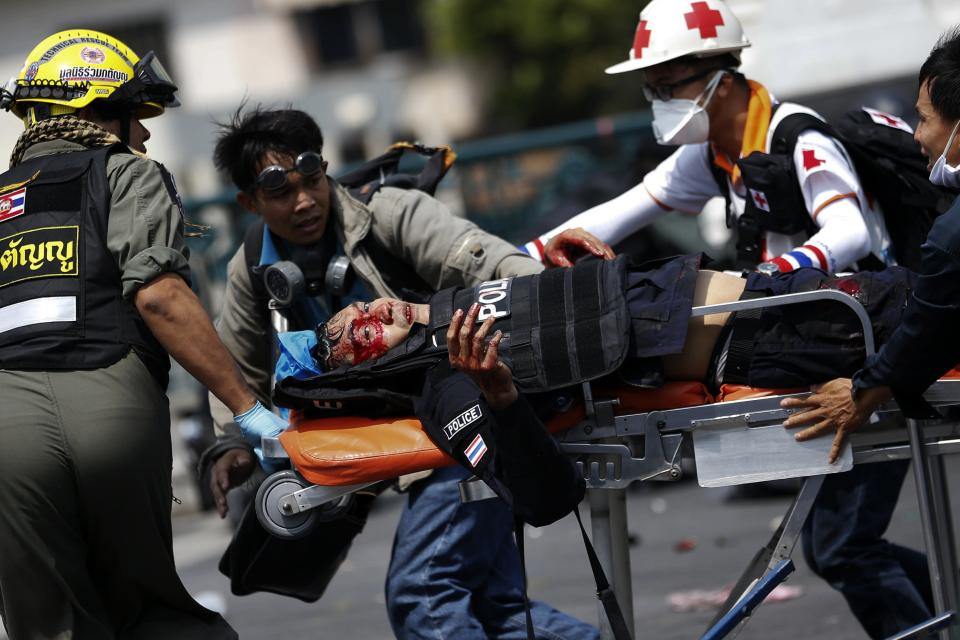 A wounded policeman is transported on a stretcher during clashes with anti-government protesters near the Government House in Bangkok February 18, 2014. A Thai police officer was killed and dozens of police and anti-government protesters were wounded in gun battles and clashes in Bangkok on Tuesday, officials and witnesses said. REUTERS/Damir Sagolj (THAILAND - Tags: POLITICS CIVIL UNREST)