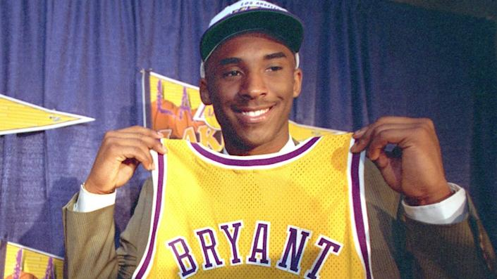Lakers guard Kobe Bryant holds up his jersey during his introductory news conference on July 12, 1996.