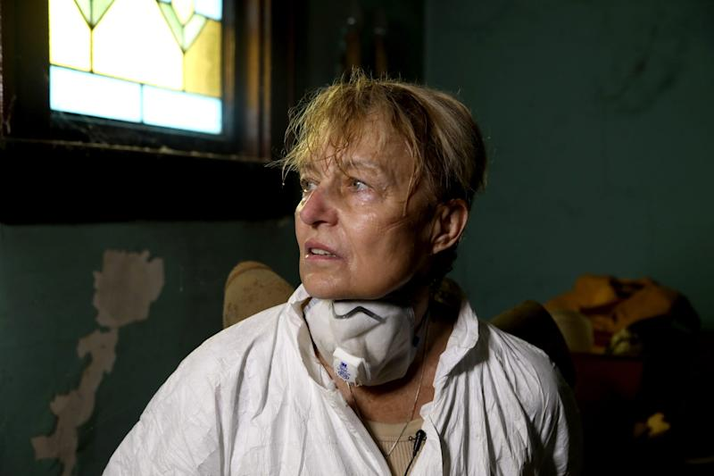 A sweaty Linda Kajma takes a break from cleaning out the front room of the house in Detroit that belonged to Sally and Lorraine Honeycheck, cousins of her mother on Saturday, July 6, 2019. Because of the smell from rat urine and droppings, untold amounts of mold and other items in the house Kajma has to wear non-breathable hazmat suit and mask for her safety.