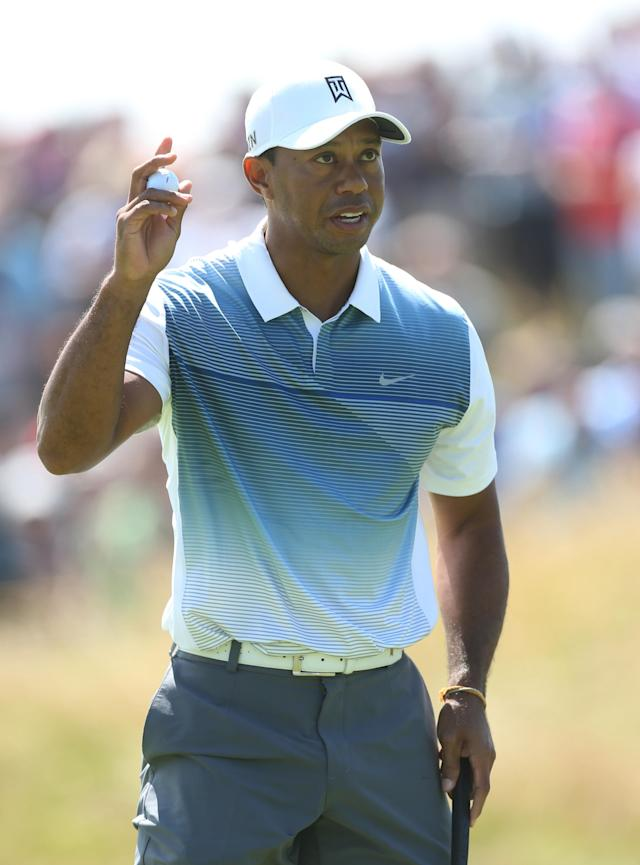 Tiger Woods of the US holds up his ball after putting out on the 11th green during the first day of the British Open Golf championship at the Royal Liverpool golf club, Hoylake, England, Thursday July 17, 2014. (AP Photo/Peter Morrison)