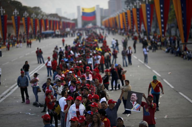 People line up to see the body of Venezuela's late President Hugo Chavez outside the military academy where he is lying in state in Caracas, Venezuela, Saturday, March 9, 2013. Chavez died on March 5, 2013 after a nearly two-year bout with cancer. He was 58. (AP Photo/Rodrigo Abd)