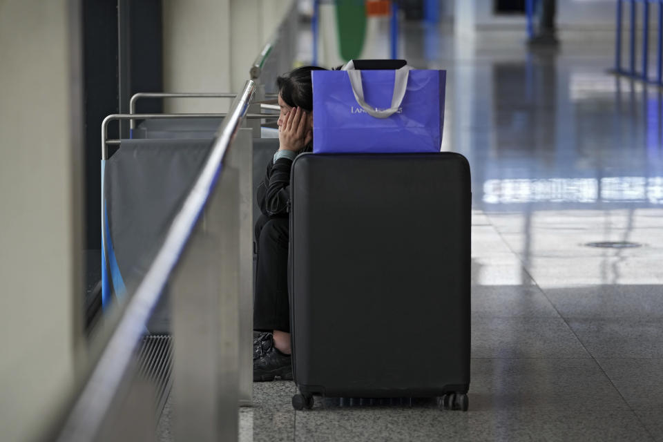 A passenger reacts as she sits near her luggage after all flights were cancelled at Pudong International Airport in Shanghai, China, Sunday, July 25, 2021. Airline flights were canceled in eastern China and cargo ships were ordered out of the area Saturday as Typhoon In-fa churned toward the mainland after dumping rain on Taiwan. (AP Photo/Andy Wong)