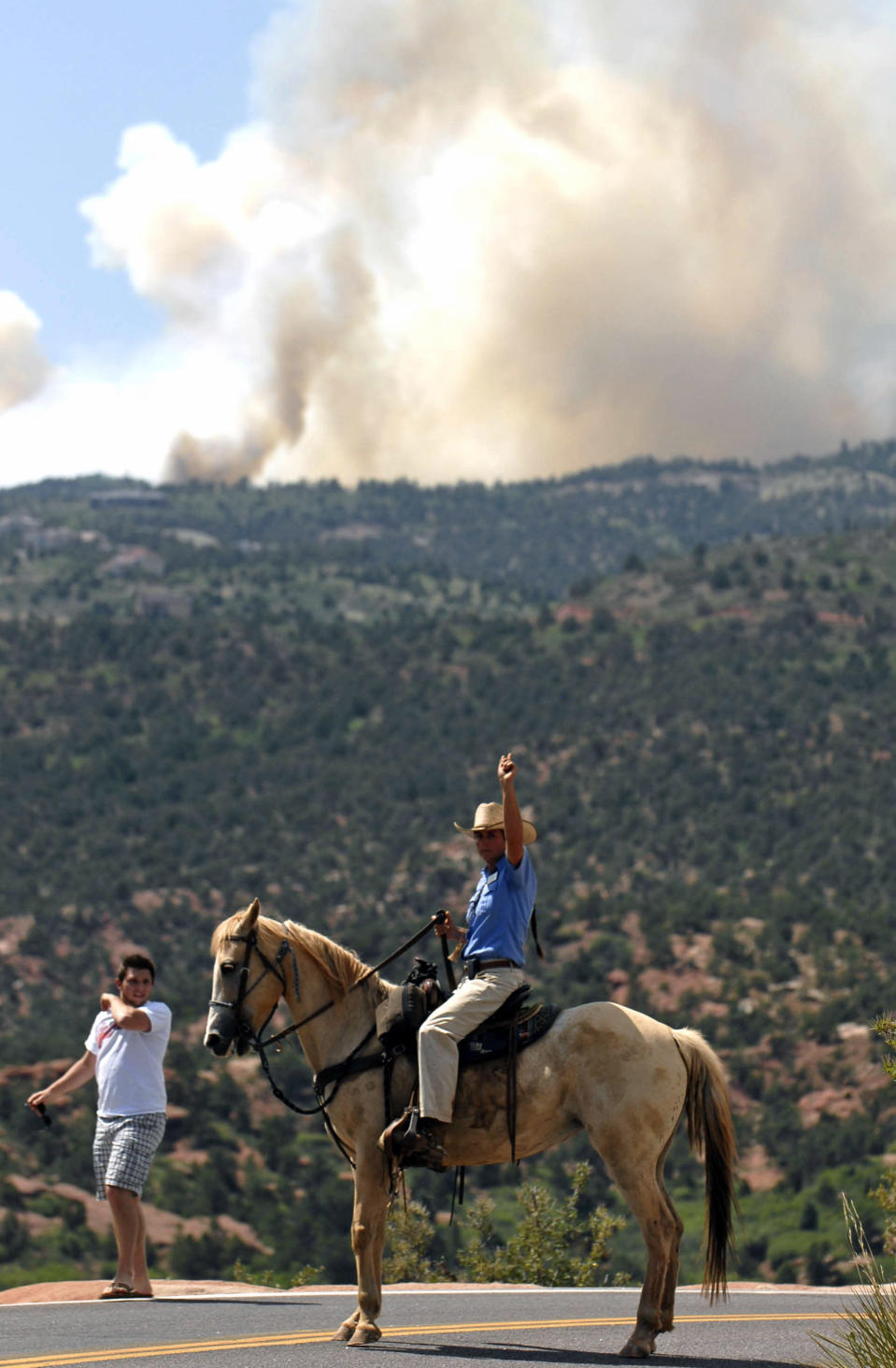 Stephanie Stover, with the City of Colorado Springs, directs traffic away after a mandatory evacuation was announced for the Garden of The Gods due to a wildfire burning west of Colorado Springs, Colo. on Saturday, June 23, 2012. The fire has grown to an estimated 600 acres and The Gazette reports authorities are evacuating the exclusive Cedar Heights neighborhood as well as the Garden of the Gods. (AP Photo/Bryan Oller)