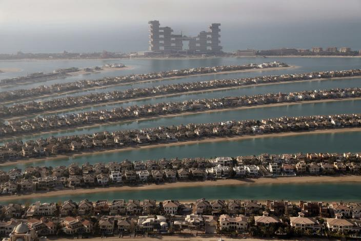Villas one the fronds of the Jumeirah Palm Island are seen from the observation deck of The View at The Palm Jumeirah, in Dubai, United Arab Emirates, Tuesday, April 6, 2021. Foreign buyers flush with cash have flooded the high-end property market in Dubai even as coronavirus vaccines roll out unevenly across the world and waves of infections force countries to extend restrictions. It's one of the few places in the world where they can dine, shop and do business in person. (AP Photo/Kamran Jebreili)