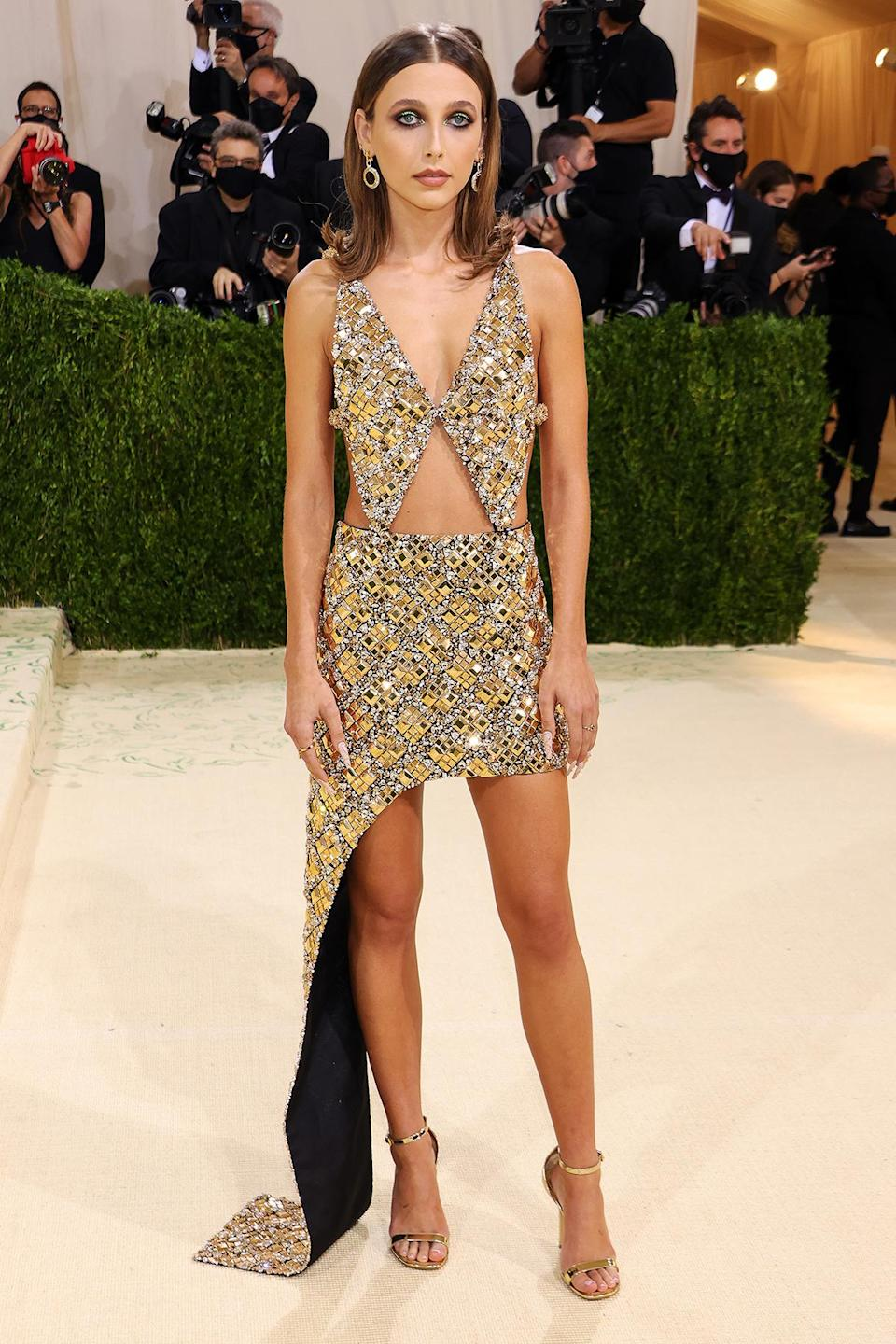 <p>wearing embroidered golden Louis Vuitton with coordinating jewelry and sandals by the brand.</p>