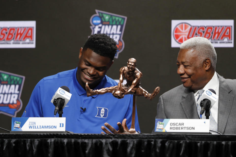 Duke freshman Zion Williamson sits behind the Oscar Robertson Trophy with National Collegiate Basketball Hall of Fame member Oscar Robertson at a news conference where Williamson was awarded the U.S. Basketball Writers Association College Player of the Year award at the Final Four NCAA college basketball tournament, Friday, April 5, 2019, in Minneapolis. (AP Photo/Charlie Neibergall)