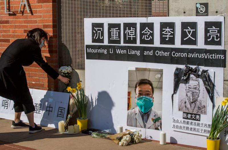 Chinese students and their supporters hold a memorial for Dr Li Wenliang, who was the whistleblower of the Coronavirus, Covid-19, that originated in Wuhan, China outside the UCLA campus in Westwood, California, on February 15, 2020. (Photo by Mark RALSTON / AFP) (Photo by MARK RALSTON/AFP via Getty Images)