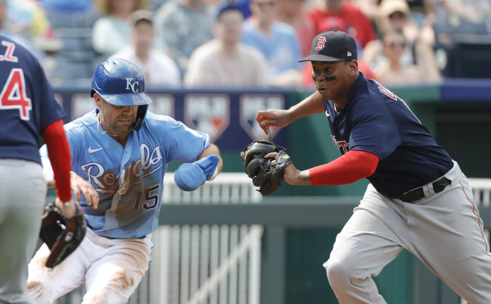 Kansas City Royals' Whit Merrifield, left, is chased down by Boston Red Sox third baseman Rafael Devers, right, for an out during a rundown between home plate and third base in the third inning of a baseball game at Kauffman Stadium in Kansas City, Mo., Saturday, June 19, 2021. (AP Photo/Colin E. Braley)