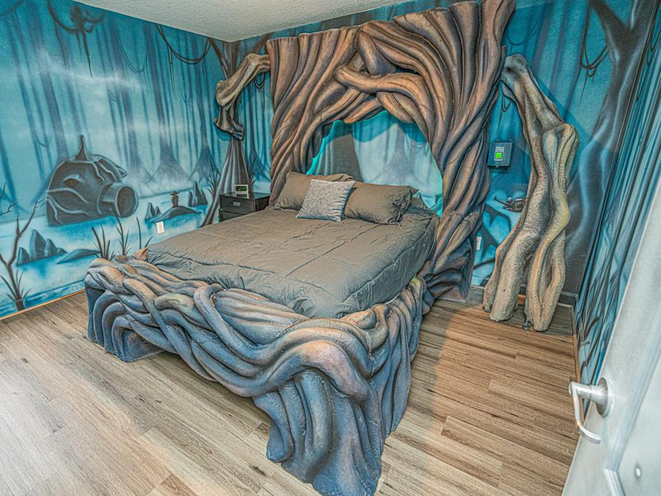 """The bed is surrounded by gnarled tree trunks. <p class=""""copyright"""">Loma Homes</p>"""