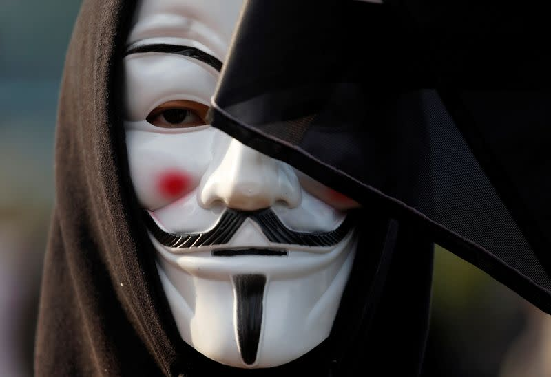 An anti-government demonstrator wearing a Guy Fawkes mask takes part in a protest at Edinburgh Place in Hong Kong