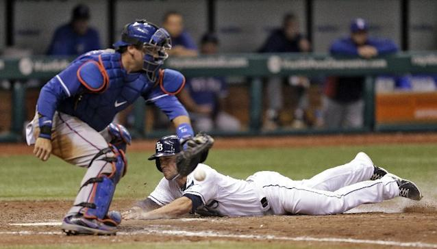 Tampa Bay Rays' Sam Fuld, right, slides home ahead of the tag by Texas Rangers catcher A.J. Pierzynski on a 12th-inning single by teammate Desmond Jennings hit off Rangers pitcher Joe Ortiz during a baseball game on Wednesday, Sept. 18, 2013, in St. Petersburg, Fla. The Rays won the game 4-3. (AP Photo/Chris O'Meara)