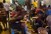 Displaced Haitians eat in a shelter for refugees, after armed gangs set their homes on fire in Port au Prince, Haiti, Thursday, June 24, 2021.Insecurity continues throughout the country with Port-au-Prince being the most-affected. (AP Photo/Joseph Odelyn)