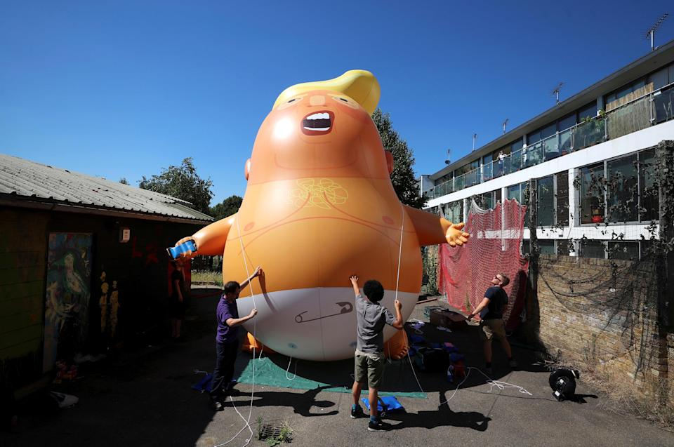 People inflate a helium filled Donald Trump blimp which they hope to deploy during The President of the United States' upcoming visit, in London. (REUTERS/Simon Dawson)