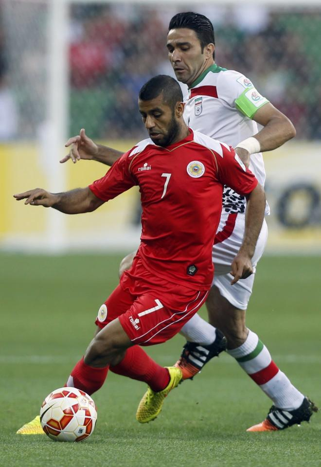 Iran's Javad Nekounam (R) and Bahrain's Abdulwahab Ali fight for the ball during their Asian Cup Group C soccer match at the Rectangular stadium in Melbourne January 11, 2015. REUTERS/Brandon Malone (AUSTRALIA  - Tags: SOCCER SPORT)