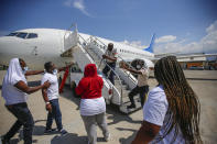 Police officers try to block a deportee from boarding the same plane he and others were deported in, to attempt to return to the United States, on the tarmac of the Toussaint Louverture airport in Port-au-Prince, Haiti Tuesday, Sept. 21, 2021 (AP Photo/Joseph Odelyn)