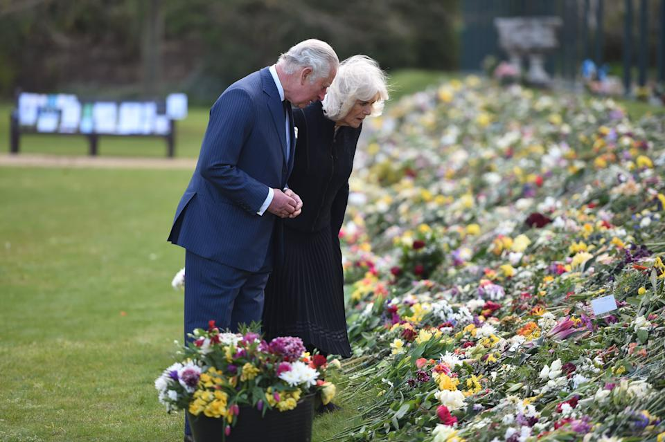 Prince Charles and Camilla looking at flowers at Prince Philip's memorial