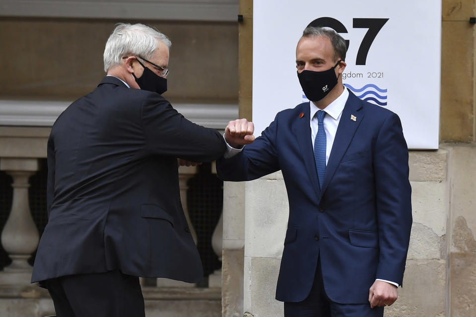 Canada's Foreign Affairs Minister Marc Garneau, left, is greeted by Britain's Foreign Secretary Dominic Raab at the start of the G7 foreign ministers meeting in London Tuesday May 4, 2021. G7 foreign ministers meet in London Tuesday for their first face-to-face talks in more than two years. (Ben Stansall / Pool via AP)
