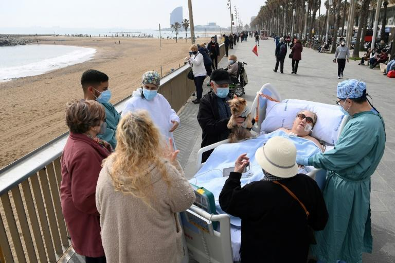 Friends, neighbours and medical personnel surround COVID-19 patient Marta Pascual, 72, as she gets some fresh air at the Barceloneta beach esplanade in Barcelona, Spain