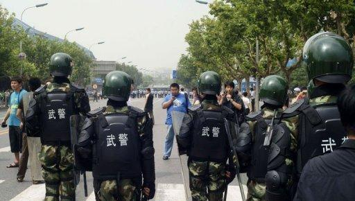 Chinese paramilitary police stand guard as hundreds of people protest against the building of the Fujia chemical plant in Dalian, in northeast China's Liaoning province, on August 14. An influential Chinese newspaper has urged citizens against taking their grievances to the streets, after thousands forced the closure of the chemical plant which they said could belch out carcinogens