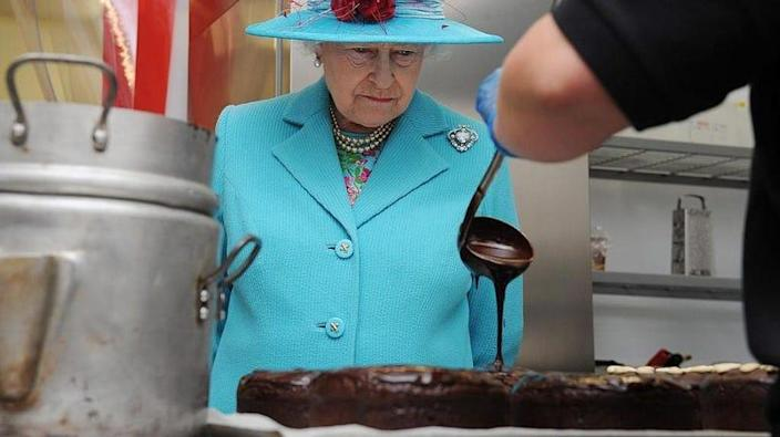 Queen Elizabeth watches as a person pours chocolate sauce out of a ladle