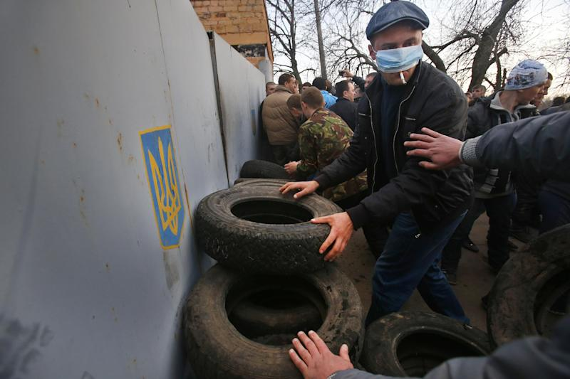 Pro-Russian activists make barricades in front of the gate of an airport in Kramatorsk, eastern Ukraine, Tuesday, April 15, 2014. In the first Ukrainian military action against a pro-Russian uprising in the east, government forces clashed Tuesday with about 30 armed gunmen at a small airport in Kramatorsk. (AP Photo/Sergei Grits)
