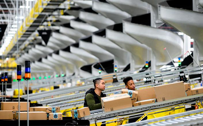 <p>Men work at a distribution station in the 855,000-square-foot Amazon fulfillment center in Staten Island, one of the five boroughs of New York City, on February 5, 2019</p> (JOHANNES EISELE/AFP via Getty Images)