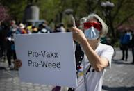 A woman holds up a sign and joints as marijuana activists hand out free joints to vaccinated New Yorkers on April 20, 2021