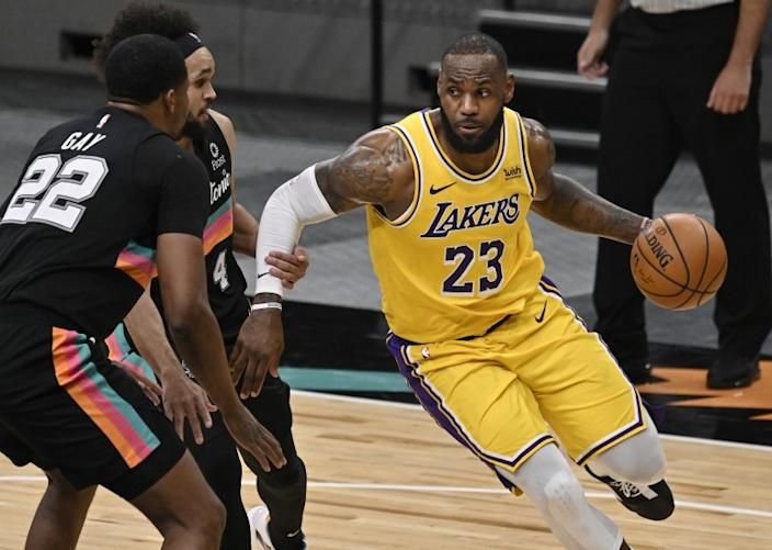 Los Angeles Lakers' LeBron James (23) drives against San Antonio Spurs' Rudy Gay (22) and Derrick White.