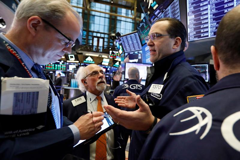 Specialist Anthony Matesic, right, works with traders on the floor of the New York Stock Exchange, Friday, Feb. 15, 2019. Stocks are opening higher on Wall Street after Chinese and U.S. officials agreed to continue trade talks in Washington next week. (AP Photo/Richard Drew)