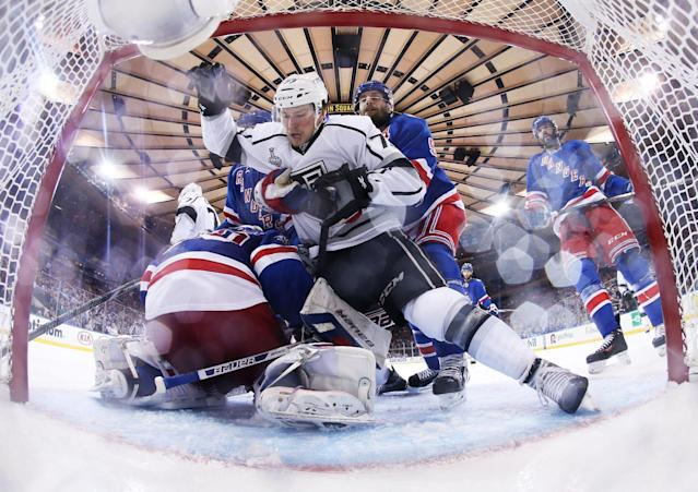 New York Rangers defenseman Dan Girardi (5) grabs Los Angeles Kings center Tyler Toffoli (73) as he falls toward the net in the third period during Game 4 of the NHL hockey Stanley Cup Final, Wednesday, June 11, 2014, in New York. The Rangers won 2-1.(AP Photo/Bruce Bennett, Pool)