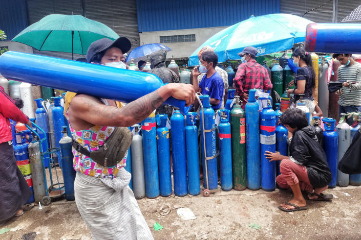 FILE - In this July 28, 2021, file photo, A man carries an oxygen tank while walking past people waiting with oxygen tanks in need of refill outside the Naing oxygen factory at the South Dagon industrial zone in Yangon, Myanmar. Supplies of medical oxygen are running low, and the government has put restrictions on its private sale in many places, saying it is trying to prevent hoarding. (AP Photo, File)