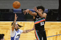 San Antonio Spurs guard Tre Jones (33) passes the ball over Orlando Magic guard Cole Anthony during the second half of an NBA basketball game, Monday, April 12, 2021, in Orlando, Fla. (AP Photo/John Raoux)