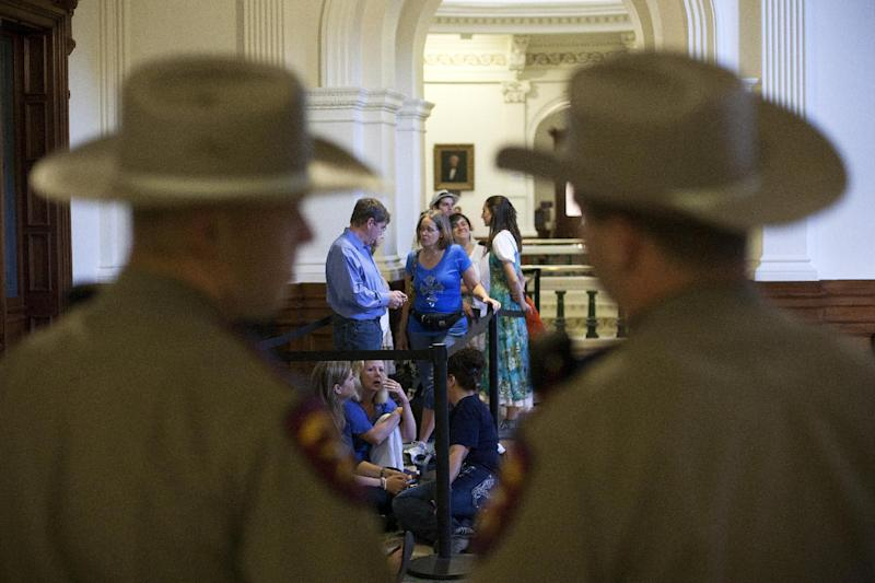Dozens wait to enter the Senate gallery moments after the Texas State Capitol opened its doors at 7 a.m., in Austin, Texas, Friday, July 12, 2013. The Texas Senate's leader, Lt. Gov. David Dewhurst, has scheduled a vote for Friday on the same restrictions on when, where and how women may obtain abortions in Texas that failed to become law after a Democratic filibuster and raucous protesters were able to run out the clock on an earlier special session. (AP Photo/Tamir Kalifa)