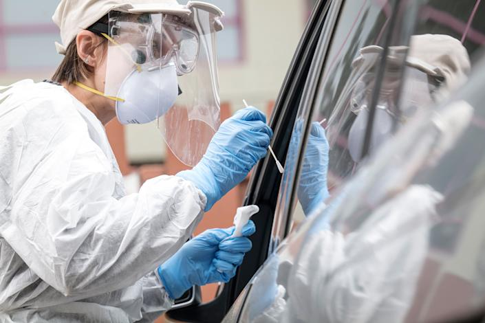 A medical worker administers a Covid-19 test at a testing site in Berkeley, California, U.S., on Friday, April 17, 2020. (David Paul Morris/Bloomberg via Getty Images)
