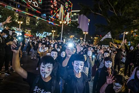 Demonstrators wearing masks protest in Tsim Sha Tsui on Tuesday. Photo: Bloomberg