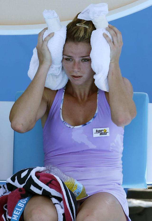 Camila Giorgi of Italy cools off with ice pack during a break as she plays Storm Sanders of Australiia during their first round match at the Australian Open tennis championship in Melbourne, Australia, Tuesday, Jan. 14, 2014