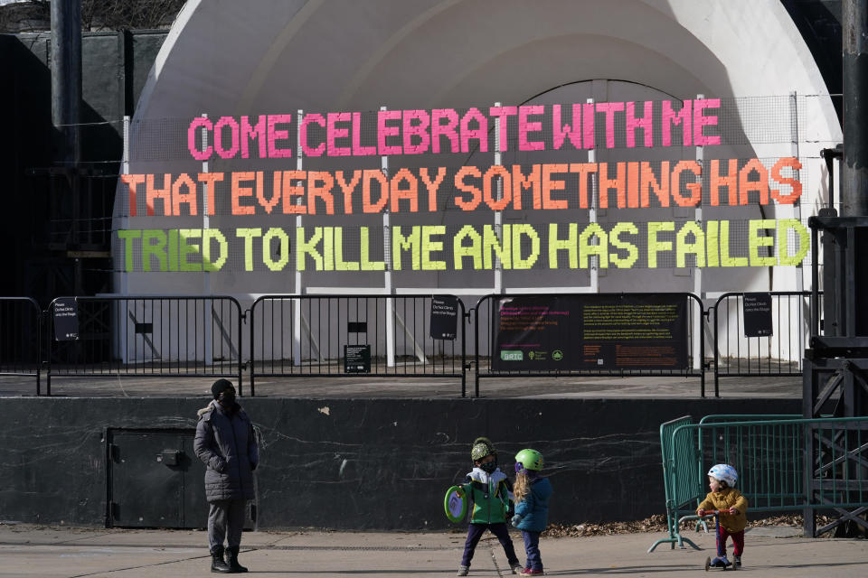 A nanny, left, watches children play in front of a text-based woven art installation spanning the stage at the Prospect Park bandshell, Monday, Jan. 25, 2021, in the Brooklyn borough of New York. (AP Photo/Kathy Willens)