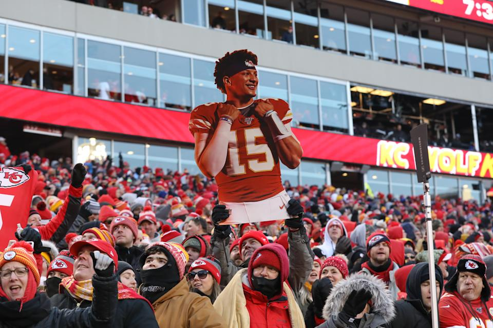 Kansas City Chiefs fans hold up a large cutout of quarterback Patrick Mahomes.