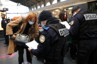 French police officers check passengers of a train from Amsterdam and Brussels at Gare du Nord station in Paris, Monday, Feb. 1, 2021. France says it's closing its borders to people arriving from outside the European Union starting Sunday to try to stop the growing spread of new variants of the virus and avoid a third lockdown. (AP Photo/Francois Mori)